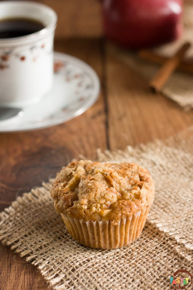 streusel topappl muffin on a table with coffe, an apple and cinnamon sticks