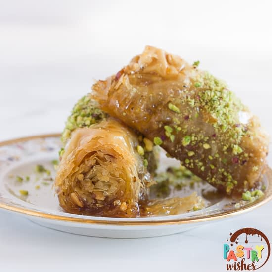 two Greek baklava rolls on a plate, covered with ground pistachios