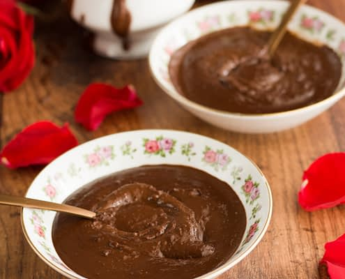 two bowls of chocolate soup with a spoon in each bowl surrounded by rose petals and a porcelain jug dripping with soup and a red satin tablecloth and a red rose in the background