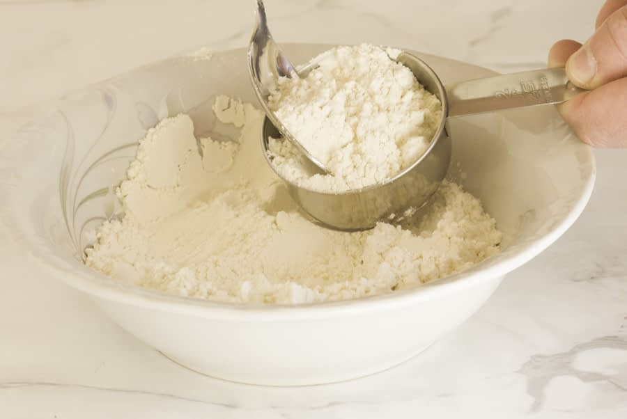 flour in a bowl and some flour being spooned into a measuring cup