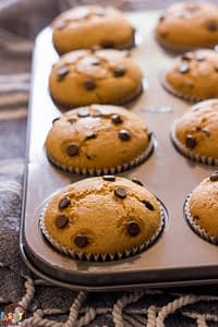 Vegan Chocolate Chip Muffins in a pan on a kitchen towel