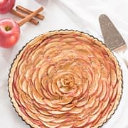 apple rose tart with kitchen towel, spatula, two apples and three cinnamon sticks