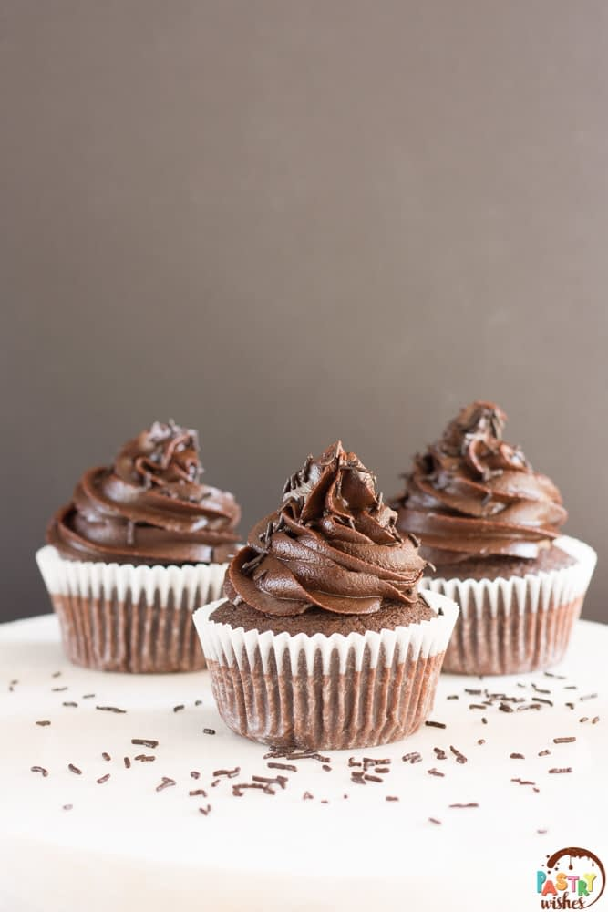 three chocolate cupcakes with dark chocolate frosting