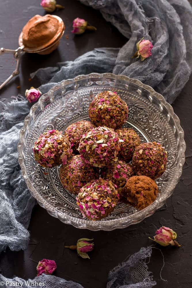 rose bliss balls in a glass bowl on a dark surface with dried rose buds, cocoa powder and gray cloth