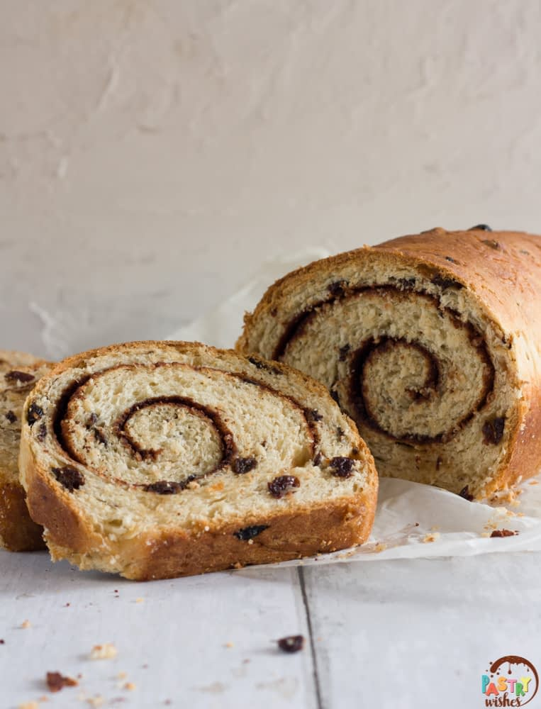 swirled cinnamon raisin bread with two slices and a loaf