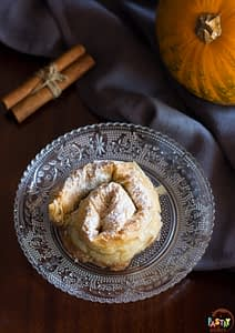 greek pumpkin hand pie on a plate with cinnamon sticks and a pumpkin