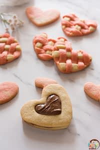 a cookie sandwich with chocolate and two toned heart sugar cookies on a white counter