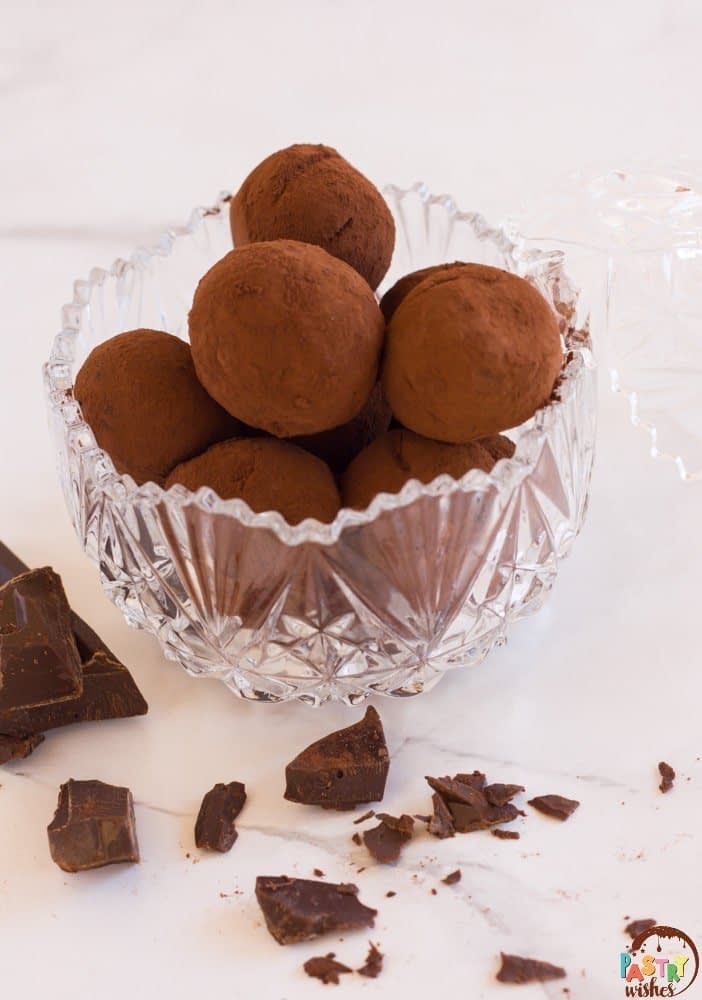 vegan chocolate truffles in a glass bowl on white surface with pieces of chocolate surrounding it