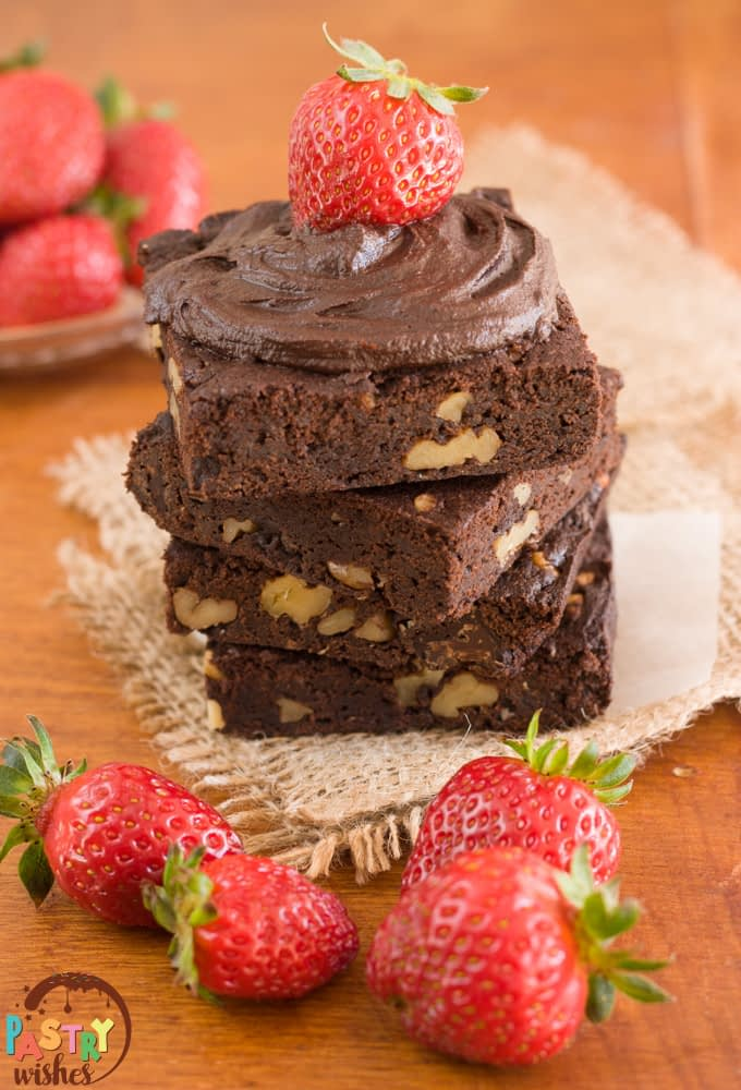 four squares of vegan fudge brownies stacked on top of each other with frosting and strawberries