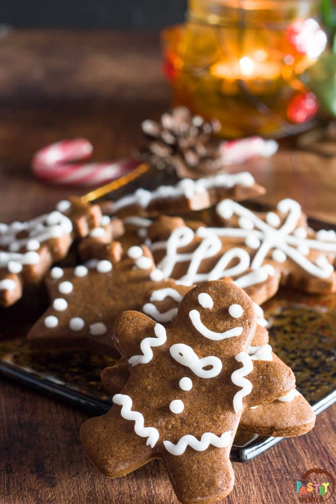grek gingerbread cookies on a plate with a candy cane and candle in the background