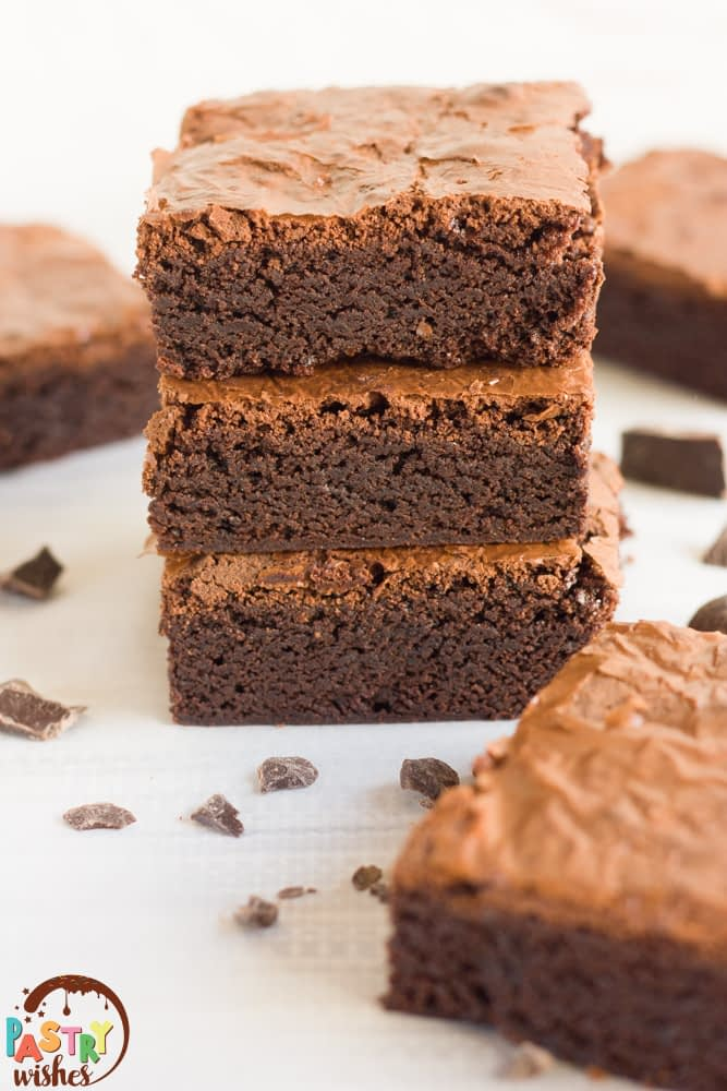 Brownies stacked on top of each other surrounded by brownies and pieces of chocolate scattered around