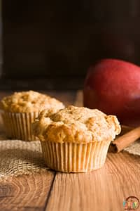 two streusel top apple muffins on wooden table with an apple and cinnamon sticks