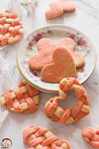 two toned heart valentine sugar cookies on a plate and white counter