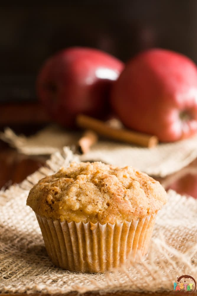 streusel top apple muffin with 2 apples and 2 cinnamon sticks
