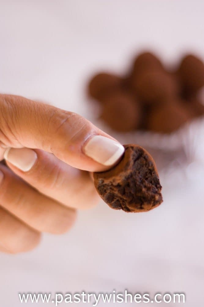 a hand holding a vegan chocolate truffle with other truffless in a glass bowl in the background