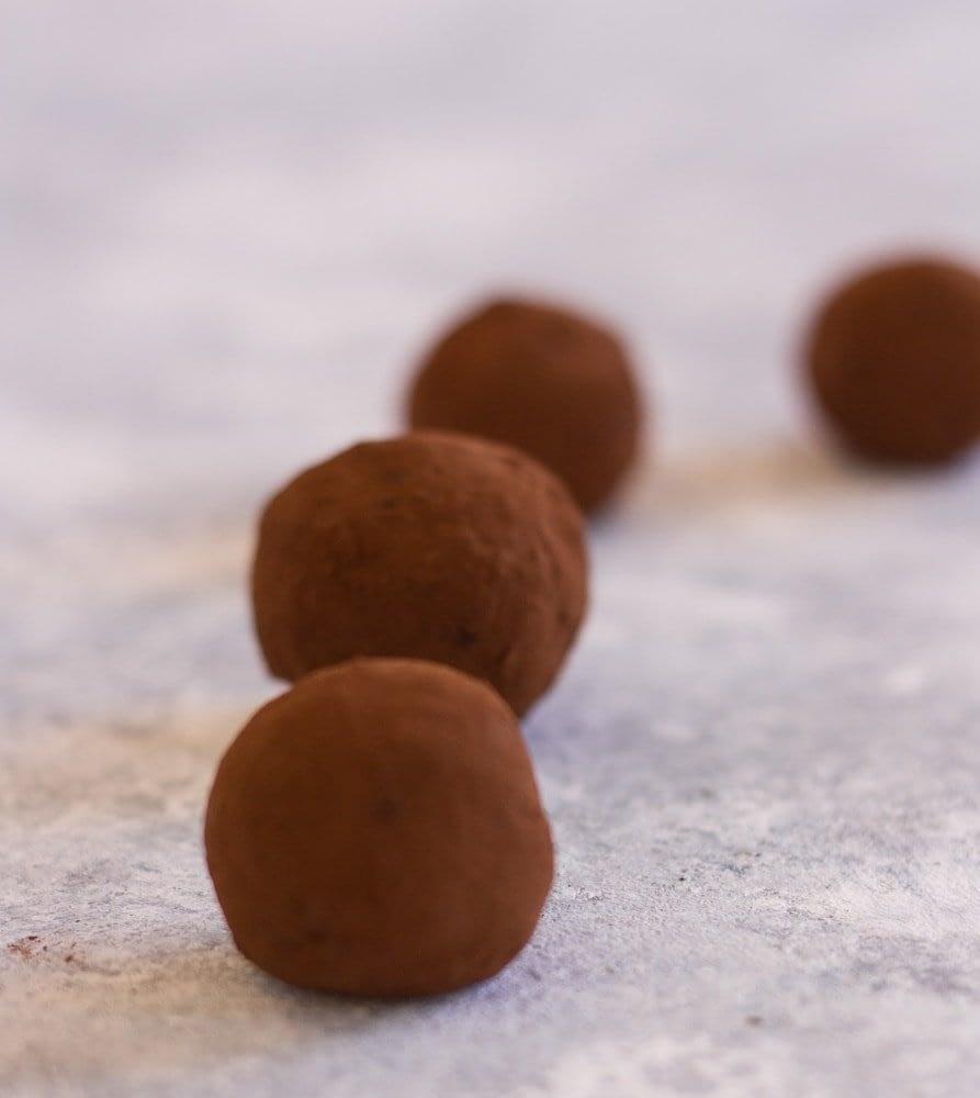 four vegan chocolate truffles in a row