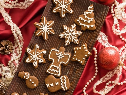 greek gingerbread cookies on a wooden tray surrounded by christmas decorations on a red satin cloth