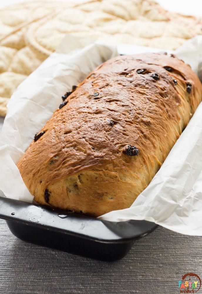 a loaf of swirled cinnamon raisin bread in a bread pan