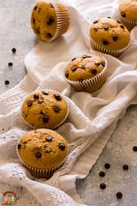 Vegan Chocolate Chip Muffins on a white towel with some chocolate chips on the countertop