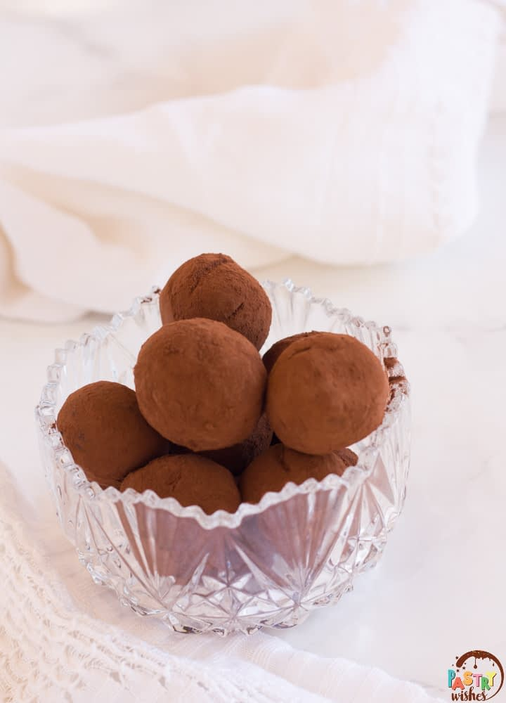 vegan chocolate truffles in a glass bowl on a white counter with a white kitchen towel in background