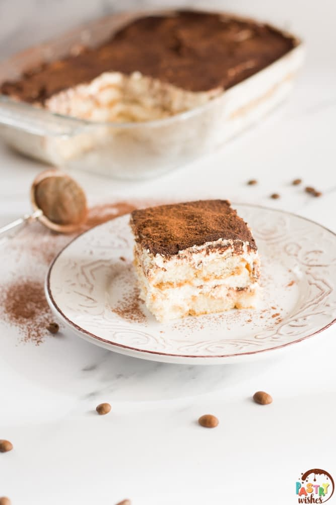 tiramisu without raw eggs on a plate on a white countertop with a pan of tiramisu in the background