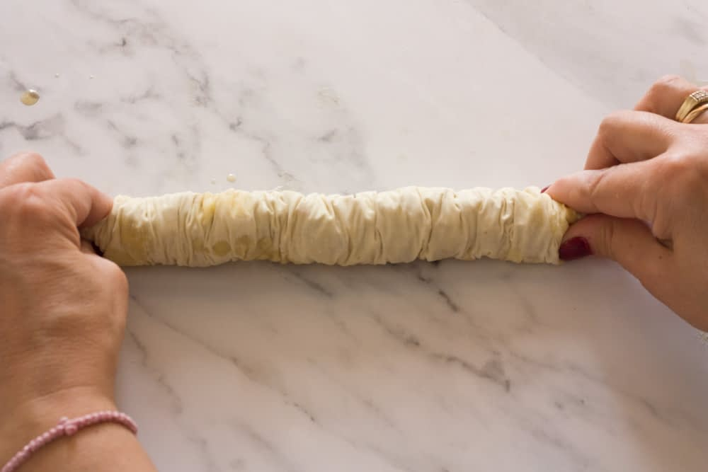 squeezing each end of a baklava saragli roll