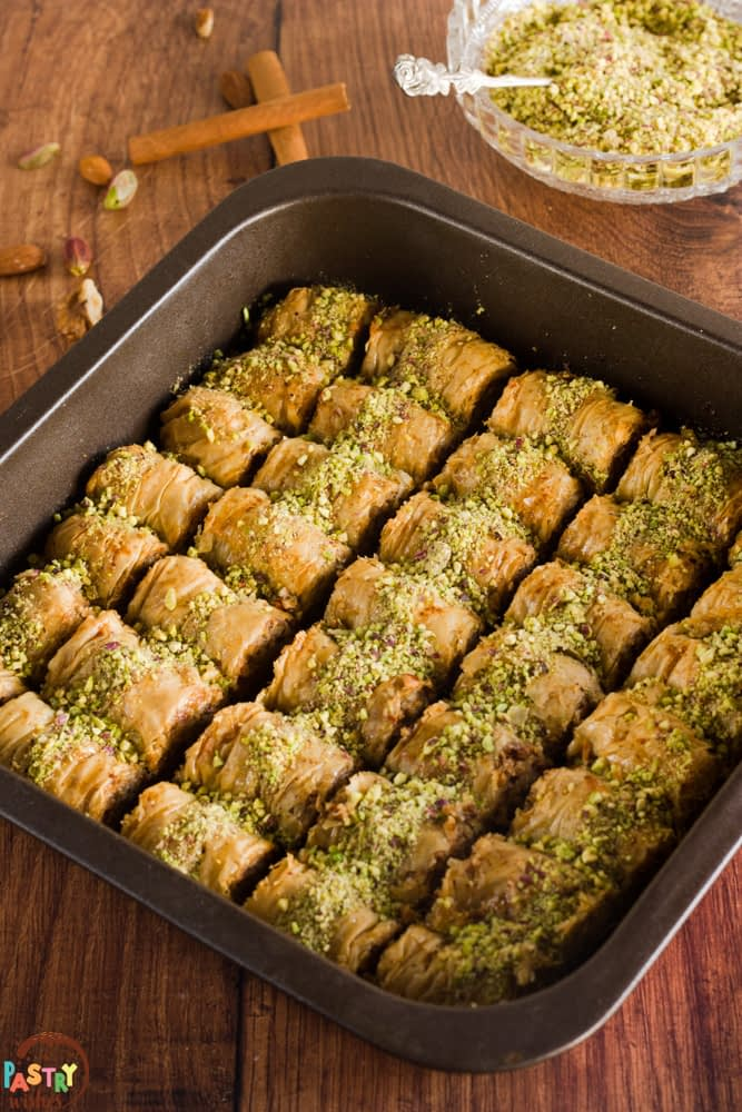 pan of saragli baklava rolls on wooden surface with nuts, cinnamon and bowl of grated pistachios in background