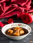 a bowl of chocolate soup with caramel brioche croutons on top and a red rose and red satin tablecloth in the background