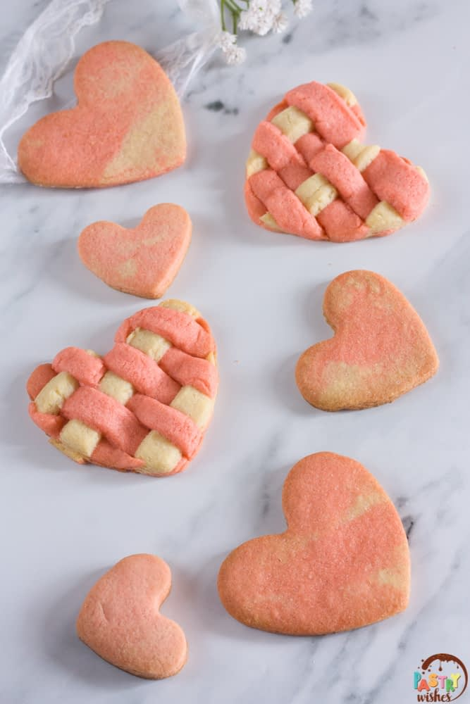 two toned valentine cookies on a white counter with lace and flowers