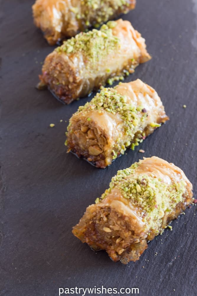 four baklava rolls, saragli on a black slate