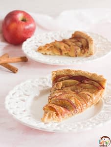 two apple rose tart slices with two cinnaom sticks, an apple and a kitchen towel