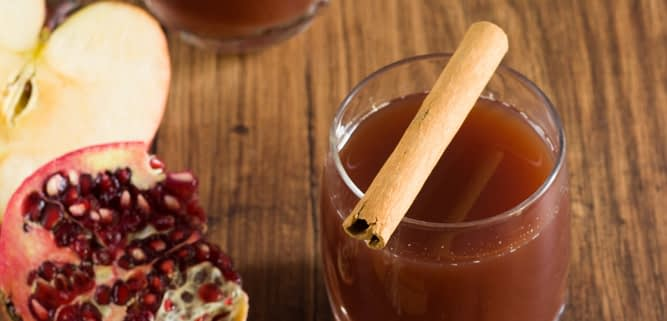 two glasses pomegranate and apple mocktail with cinnamon sticks, a sliced apple and pomegranate